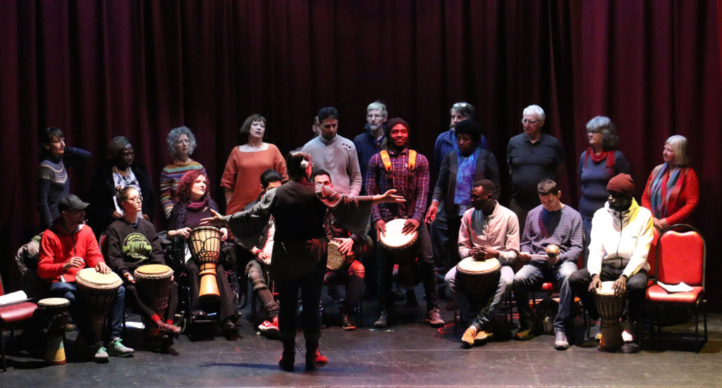 Valley and Vale Community Arts, 2018. A band making music on stage. Sat across the front row are 9 drummers, stood behind them are 12 vocalists waiting for their cue from the person stood in front of them all with their back to the camera, arms outstretched conducting.