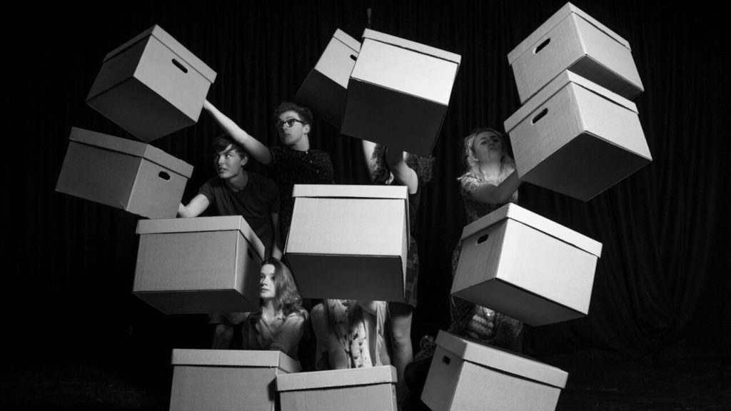Burnley youth theatre. A group of young performers thrust cardboard boxes outwards.