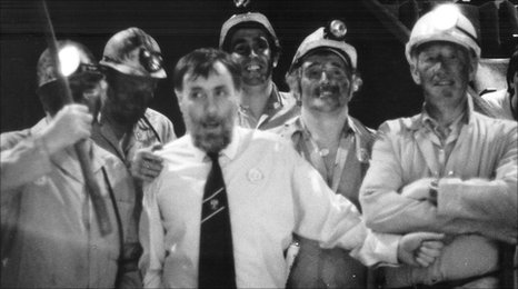 Miner Dig the Coal by Peter Cheeseman, 1966 A man in a shirt and tie, surrounded by five miners with coal on their face.