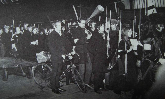 The Russian Revolution by Bradford Art College Theatre Group, 1967. A large group of men and women in long black coats hold weapons, loud speakers, one has a bike, some are carrying papers. A march.