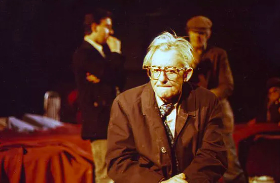 Grassmarket Project's Glad (1990). An older man in a long brown coat, shirt and tie and glasses sits pensively. A few metres behind him two younger men in suits talk with each other. One's suit and demeanor (with arms folded and a hand up in front of his mouth) suggest middle class while the other man's flat cap and outdated clothes suggest working class.