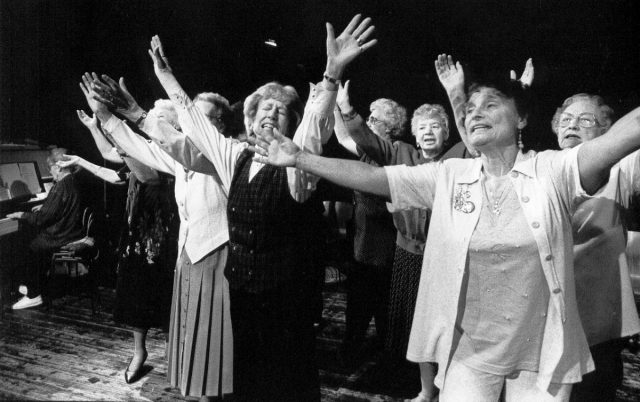 Good Companions by Age Exchange, 1979. A group of older women perform with their arms outstretched to the heavens.