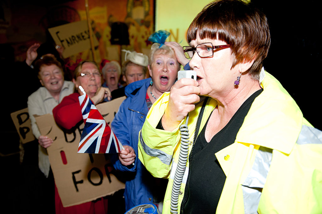 Collective Encounters' Third Age Theatre performing at In Our Times, 2012 (Photo: Ged Flemming). An older woman in a high visibility jacket speaking into a megaphone and leading a group of women of a similar age holding up placards.