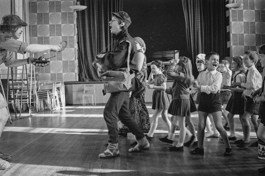 Theatre in Education from The Belgrade Theatre, 1960s (Photo: Tony Baker). A school hall. An adult male leads a pack of school children with happy faces towards another man holding a toy tank. One prominent child is howling with laughter.