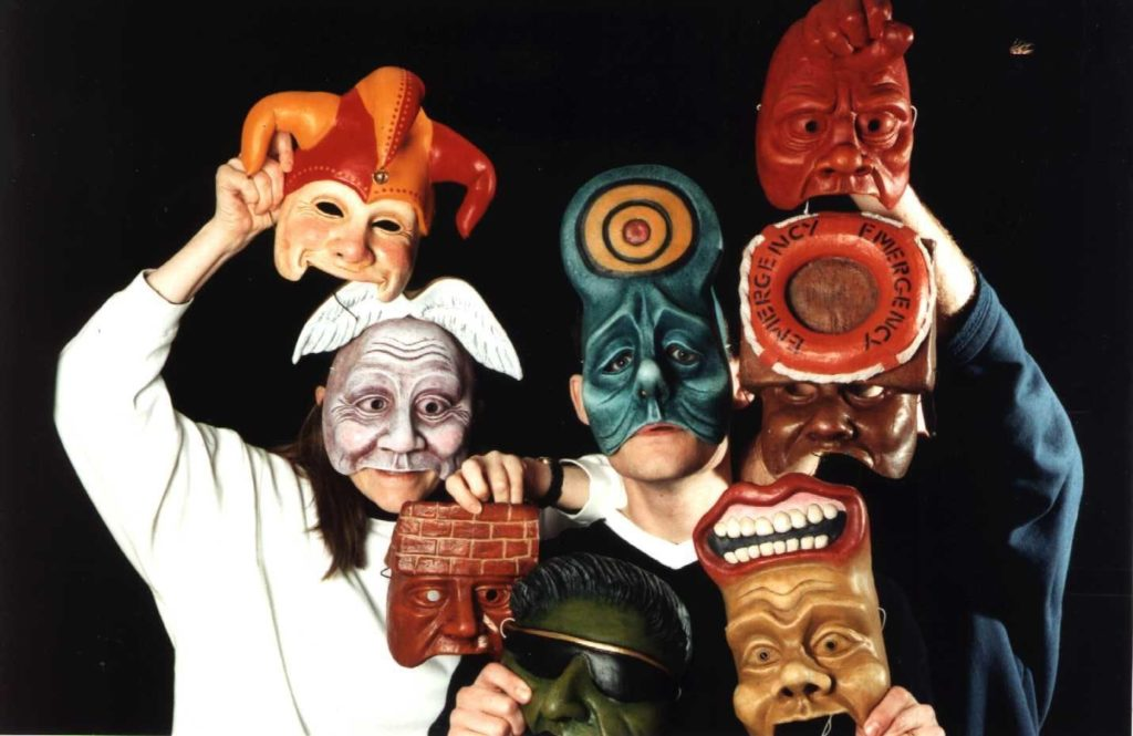 Geese Theatre's signature mask work. A group of performers in multicoloured, anthropomorphic yet still abstract masks. E.G there is a man with a brick wall for a forehead as well as a more typical harlequin mask.