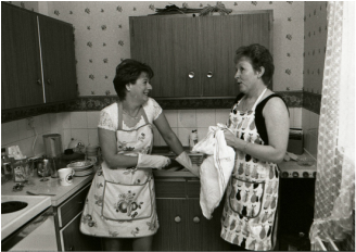 Community Arts Forum's The Wedding (1999). Two middle aged women in aprons in a kitchen washing the dishes and having a talk with a smile on their face. One dries while the other is turned away from the sink behind her to talk.