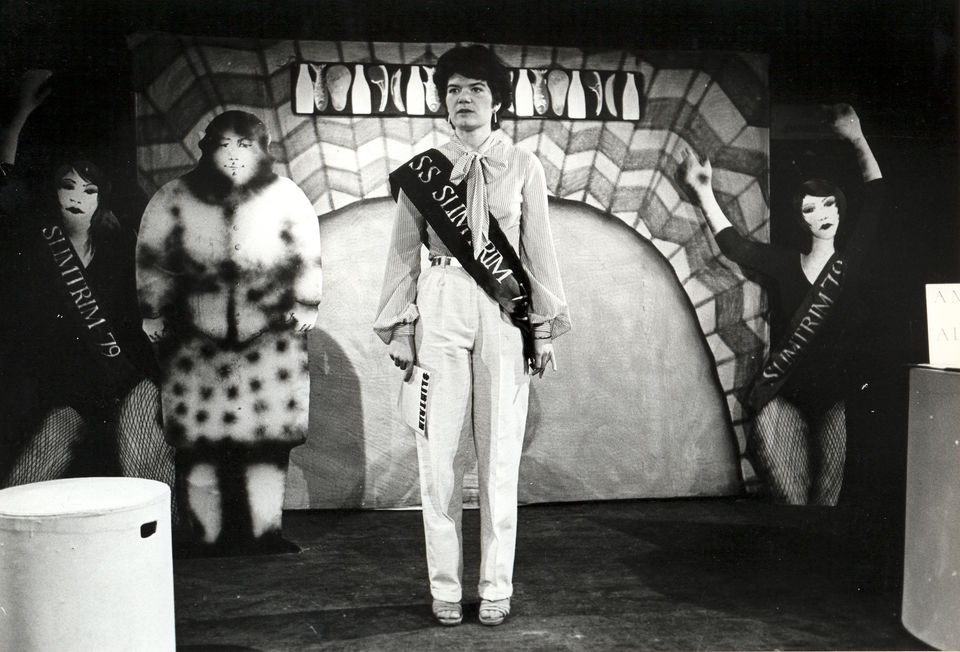 Bearing the Weight by Spare Tyre, 1979. Black and white photo of a performance inwhich a woman in a white is stood in front of a psychadelic backdrop with three two-dimensional women, one is in big furry clothes and the other two are mirror images of one another, they are a dancer in blacks.