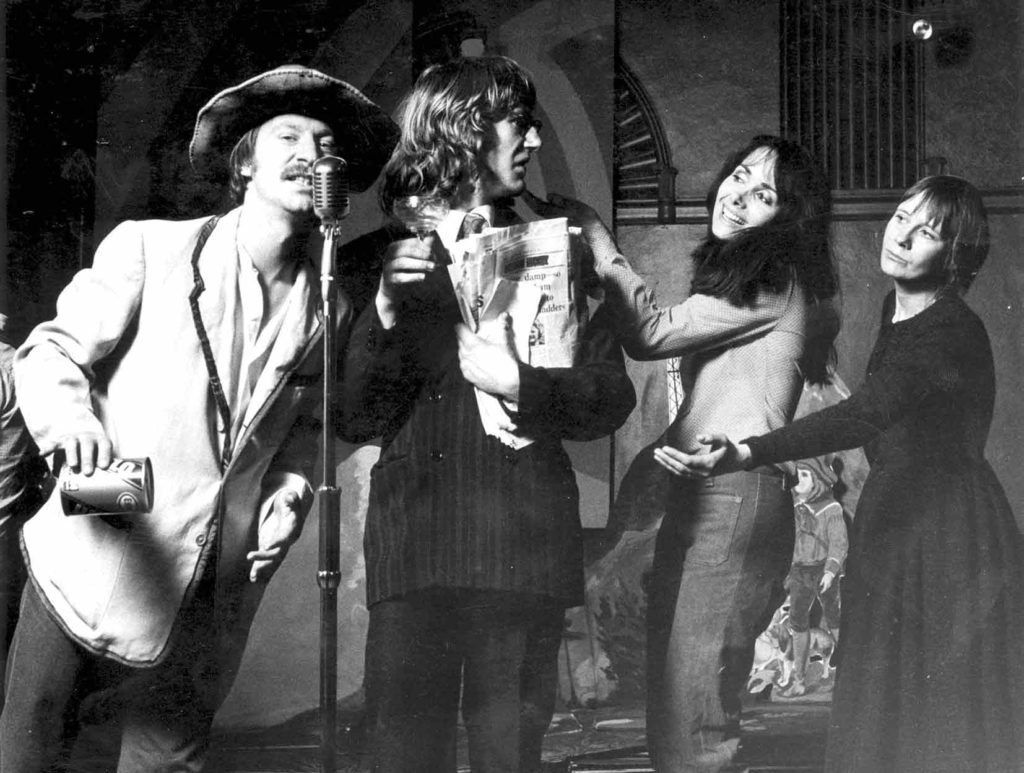 7:84's The Cheviot, The Stag and the Black, Black Oil, 1973. 4 performers on stage, two men two women. On stage right the two men, one speaks into a vintage microphone in a cheaper suit and the one next to him is in a more expensive suit holding a wad of newspapers. The two women are both communicating with the man in the more expensive suit, one with a hand on the shoulder warmly, the other with a hand outstretched expectantly.